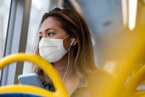 Portrait of a woman riding on a bus wearing a facemask and listening to music with headphones – public transport during the COVID-19 pandemic