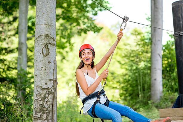 Woman riding on a zip line Young and pretty woman in red helmet riding on a zip line in the forest. Active sports kind of recreation zip line stock pictures, royalty-free photos & images