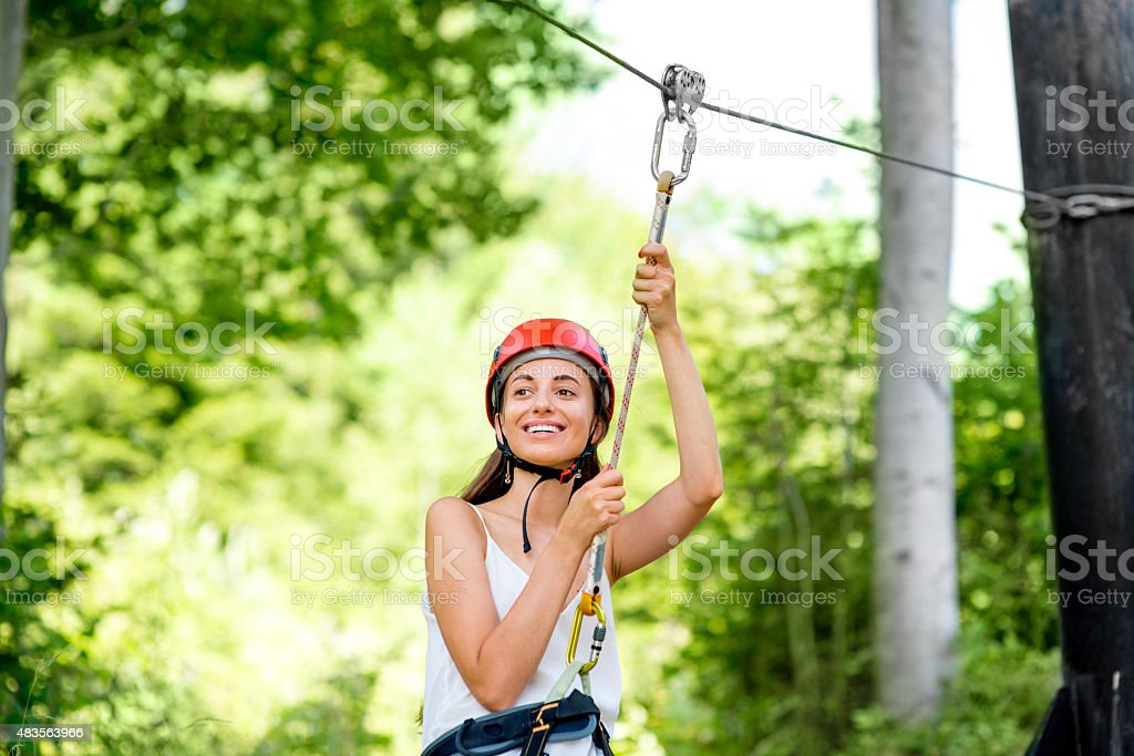 Woman riding on a zip line stock photo