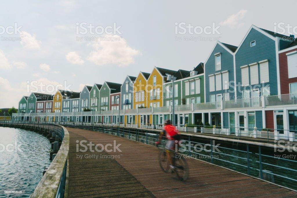 Woman riding on bicycle  near colorful buildings near the lake zbiór zdjęć royalty-free