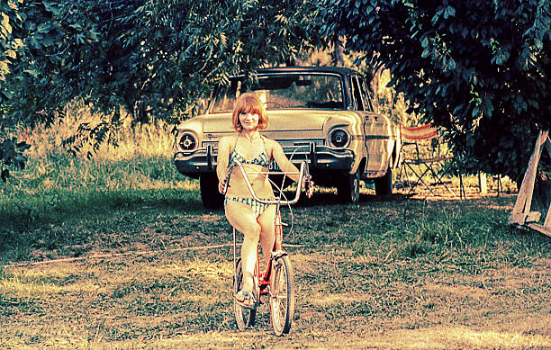 woman riding on bike in a summer day - 1970s style stock photos and pictures
