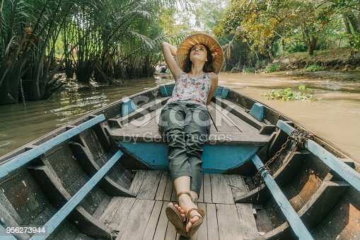 Young Caucasian woman riding on boat through Mekong delta in Vietnam