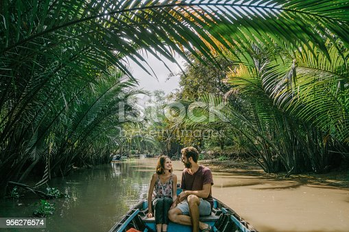 istock Woman riding on boat through Mekong delta and floating market 956276574