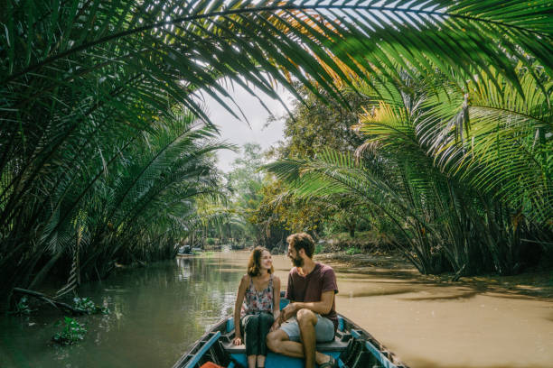woman riding on boat through mekong delta and floating market - mekong river stock pictures, royalty-free photos & images