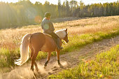 Woman horseback riding on dusty country road in the sunset
