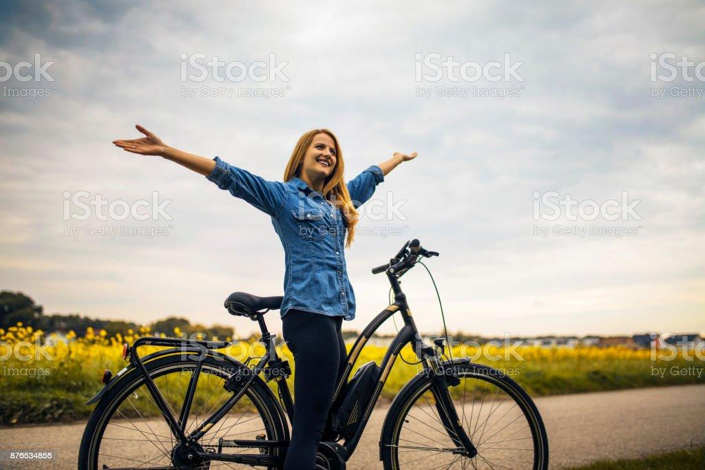 Mujer montando en su bicicleta eléctrica - foto de stock