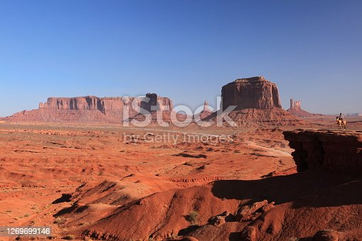 A woman riding on Horse  from John Ford's Point overlook in Monument Valley Tribal Park with the mittens and Merrick Butte in Arizona, USA