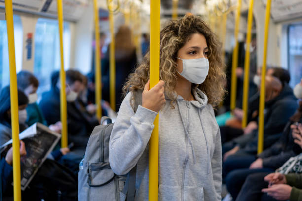 Woman riding on the metro wearing a facemask to avoid an infectious disease stock photo