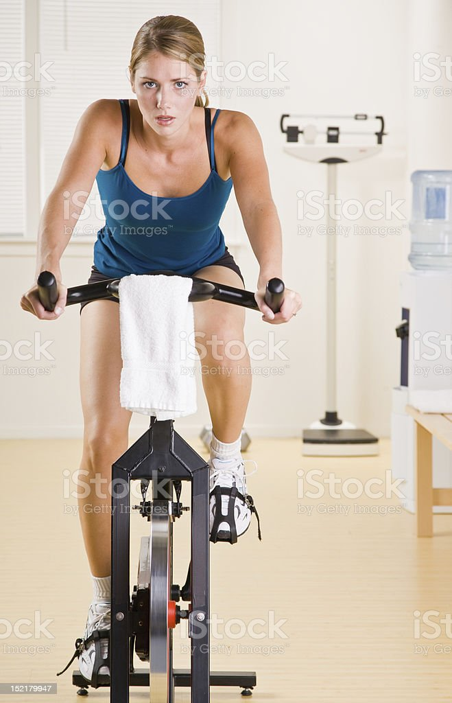 Woman riding stationary bicycle in health club stock photo