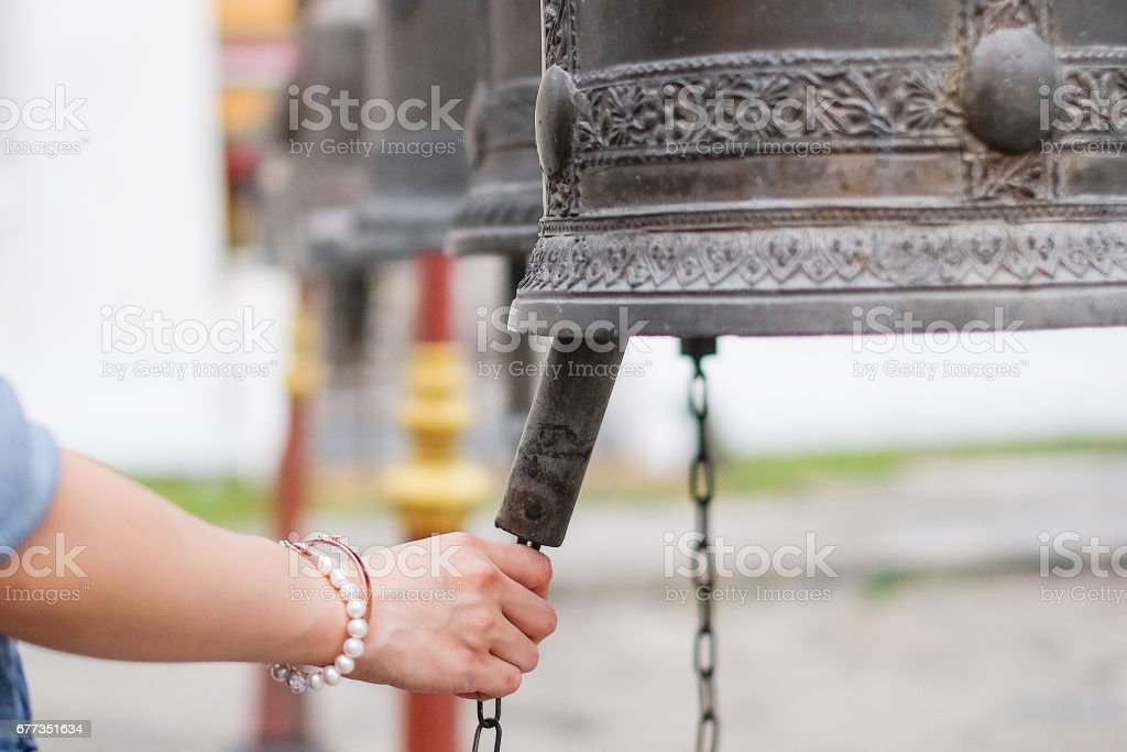 Woman ringing a bell in a Buddhist temple in Thailand stock photo