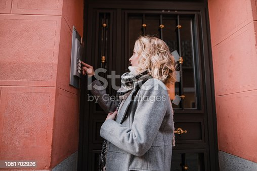 A woman ringing an apartment bell at the main entrance of a building