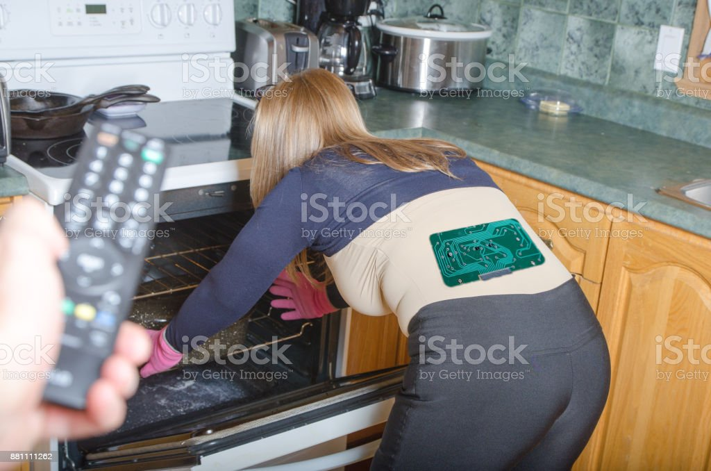 Woman robot with circuit board in back, seen from behind, putting crockery pot un oven in a house stock photo