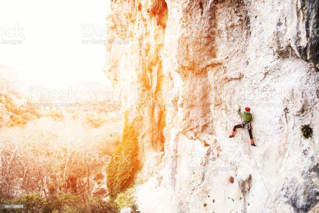 Woman rock climber. Rock climber climbs on a rocky wall. Woman makes hard move. royalty-free stock photo