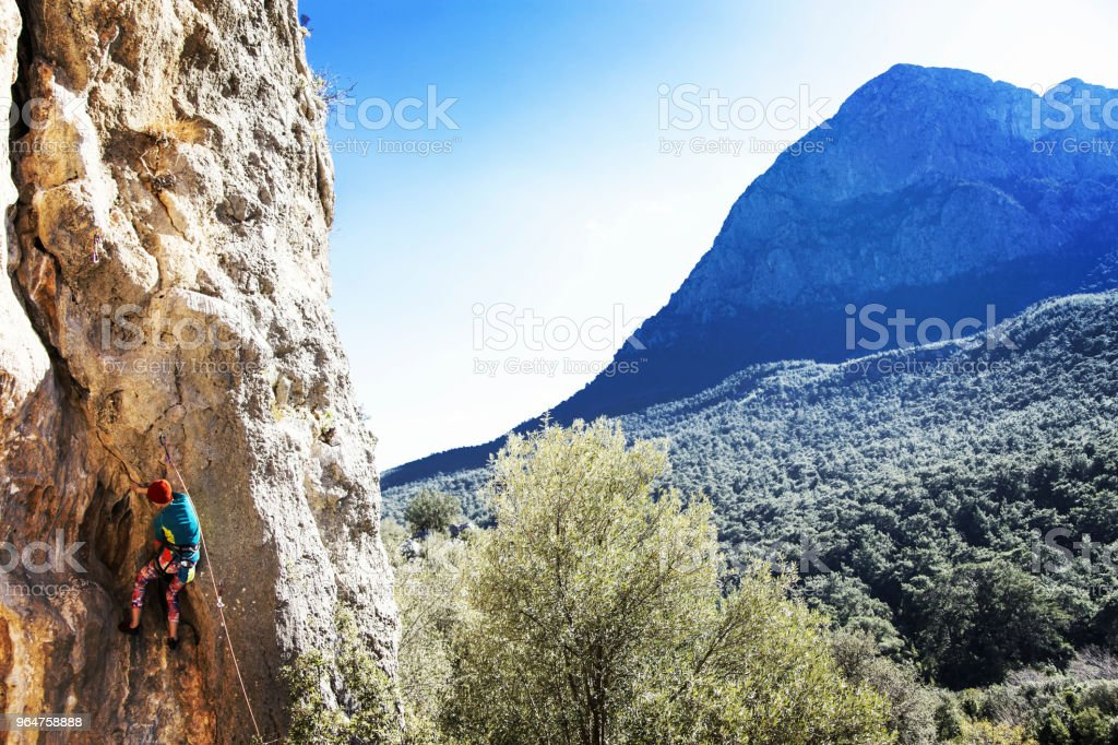 Woman rock climber. Rock climber climbs on a rocky wall. Woman makes hard move. royalty-free stock photo