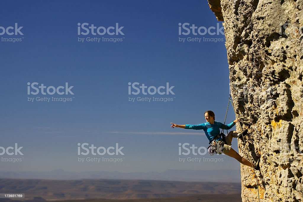 Woman rock climbing and pointing royalty-free stock photo