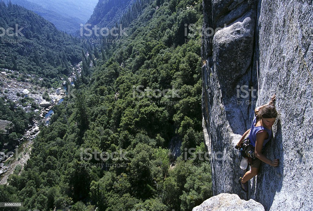 Woman rock climbing high above river royalty-free stock photo