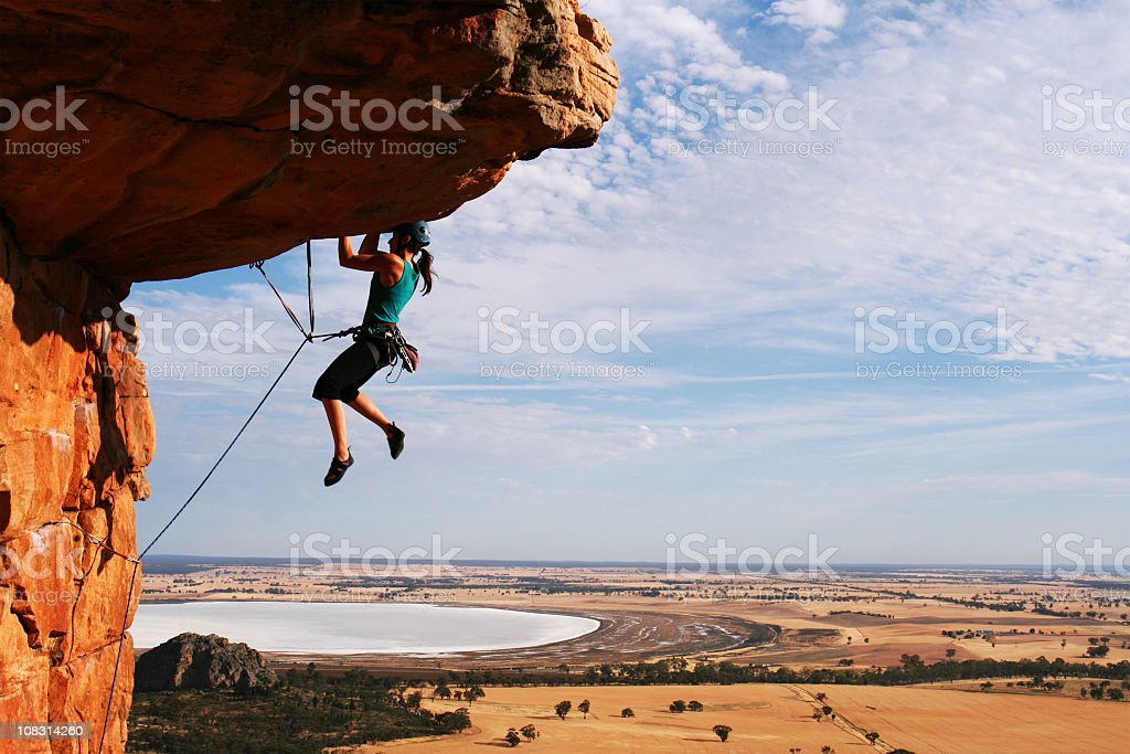 Woman rock climbing with ropes stock photo