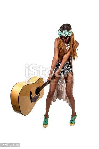 Female rock star guitarist smashing a guitar