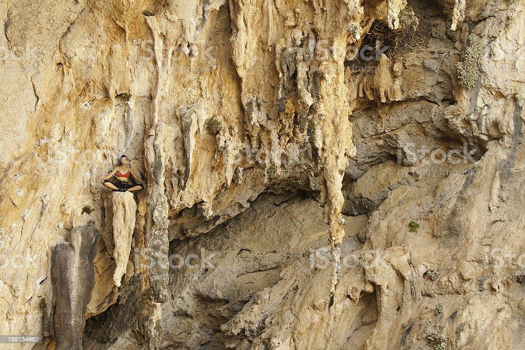 Woman rockclimbing meditating stock photo