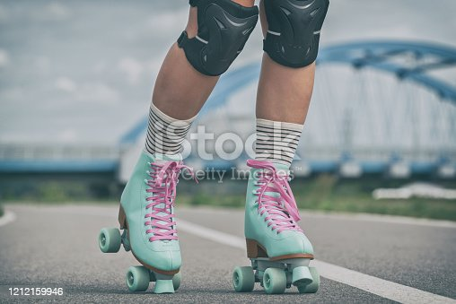 Woman rollerskater wearing knee protector pads on her leg