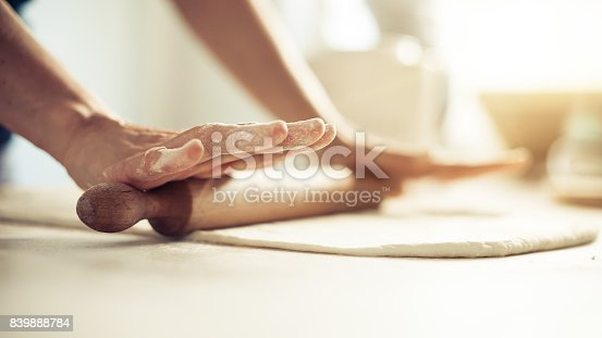 istock Woman rolling dough on wooden table with wooden rolling pin 839888784