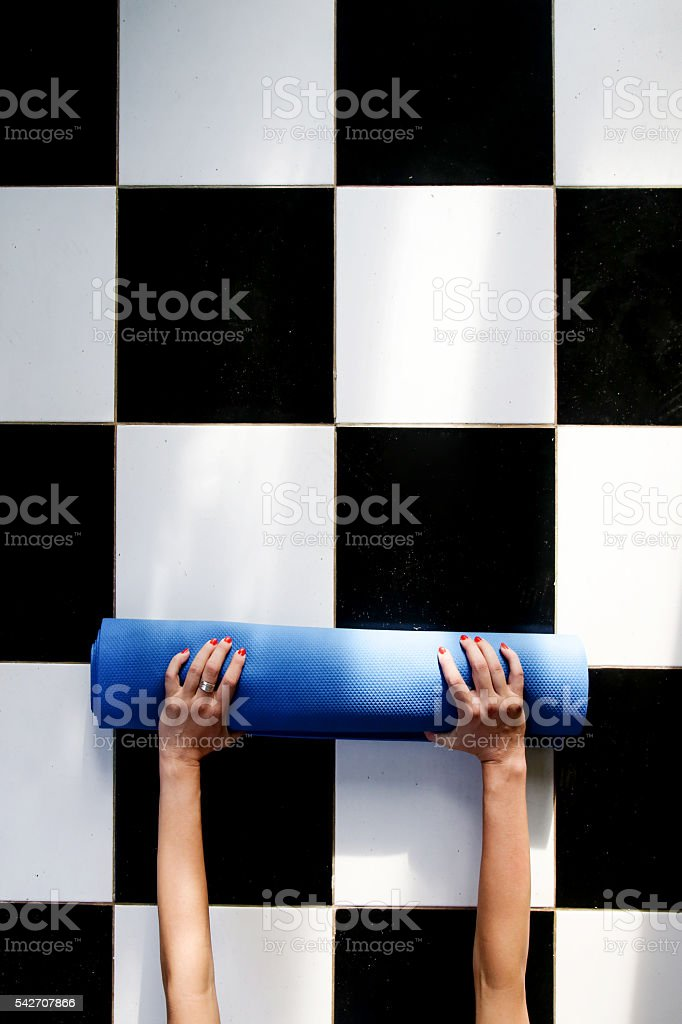 Woman rolling her mat after a yoga class stock photo
