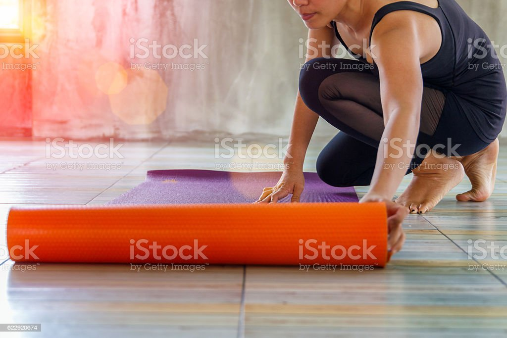 Woman rolling her mat before a yoga class stock photo