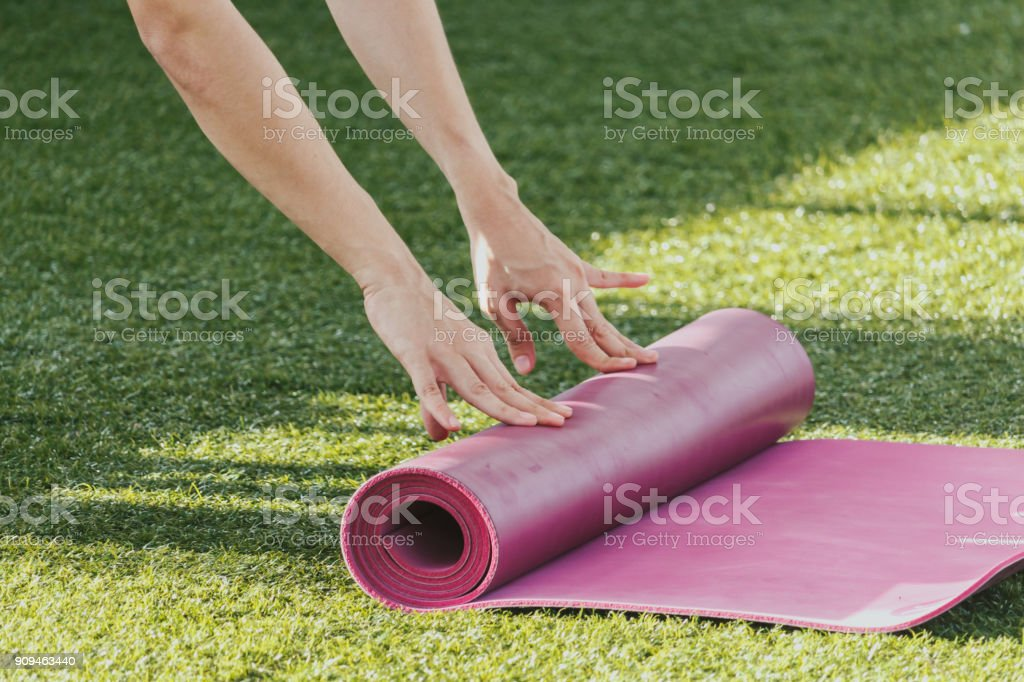 Woman rolling mat after a yoga on green grass stock photo