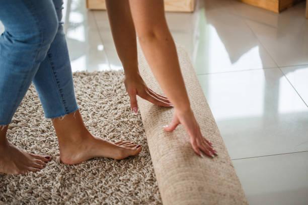 Frau rollt neuen Teppich aus – Foto