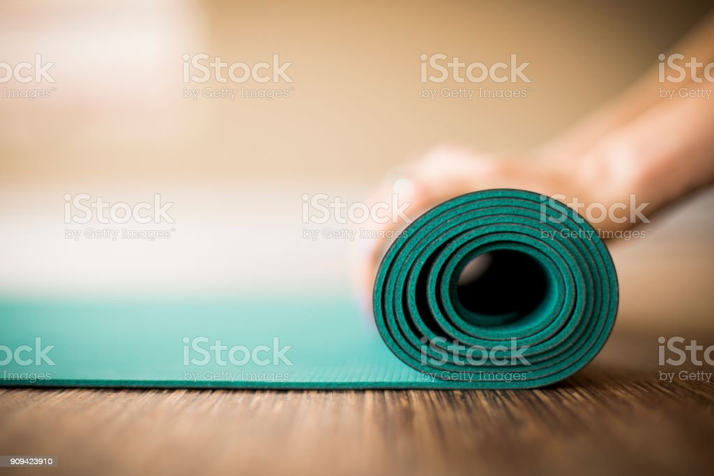 Woman rolling up yoga mat.