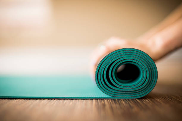 Woman rolling up yoga mat. stock photo