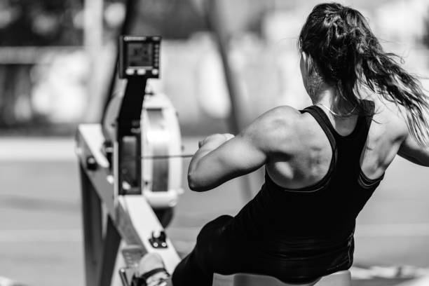 woman, rowing machine, cross training, black and white - paddeln stock-fotos und bilder