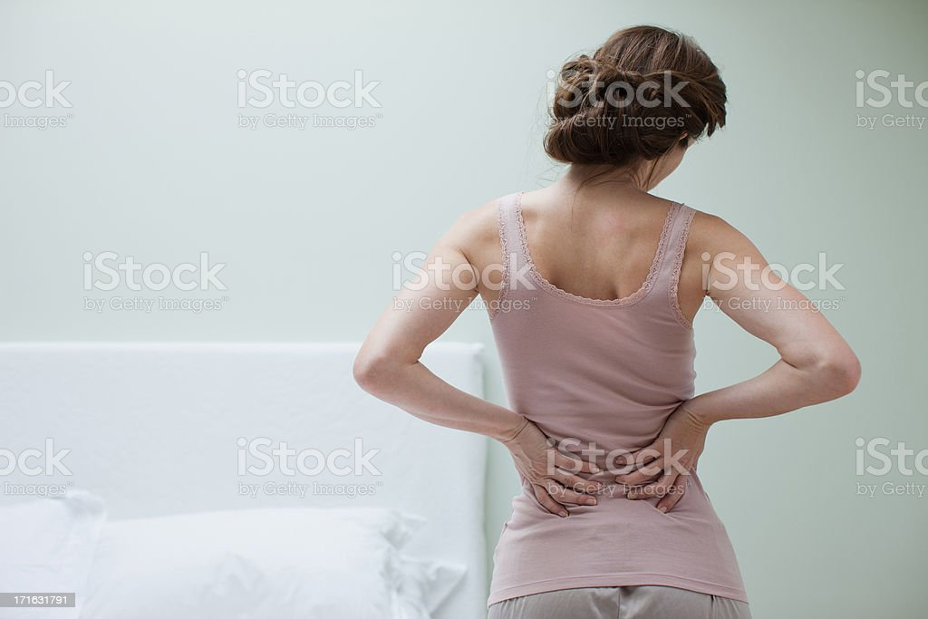 Woman rubbing aching back stock photo