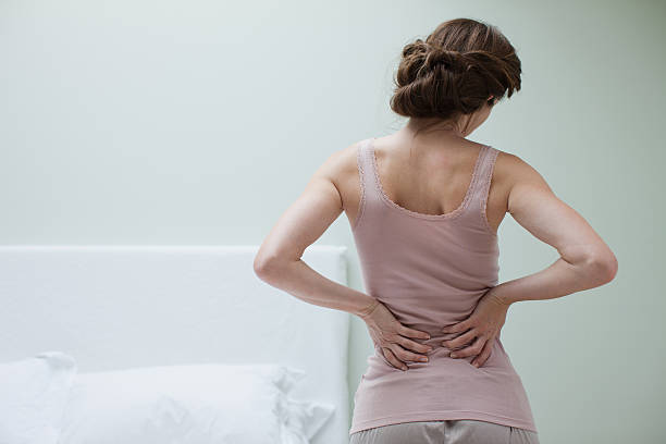 Woman rubbing aching back  back pain stock pictures, royalty-free photos & images