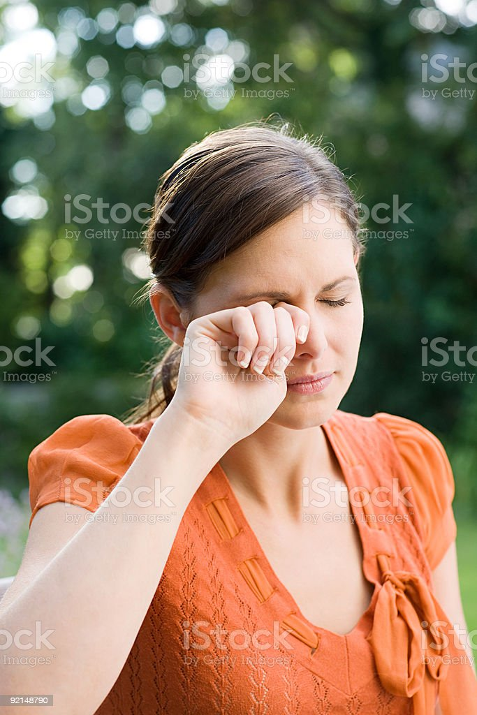 Woman rubbing eye stock photo