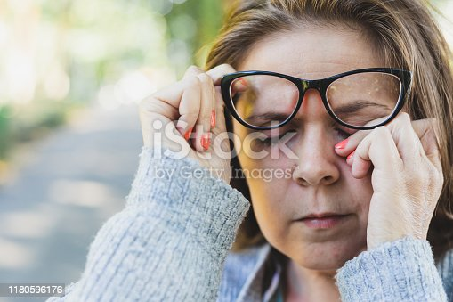 Close up shot of young woman rubbing her eye with one hand outdoors - Portrait of cute and sleepy girl with brown hair wearing eyeglasses