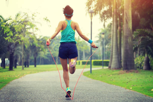 woman runner athlete jumping rope at tropical park stock photo