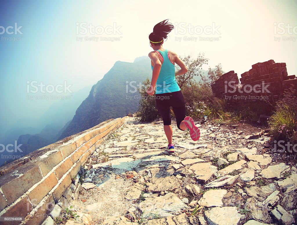 woman runner athlete running on trail at chinese great wall stock photo