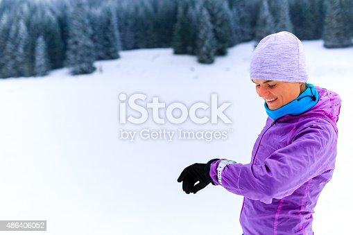 484750230 istock photo Woman runner checking sports watch on winter run 486406052