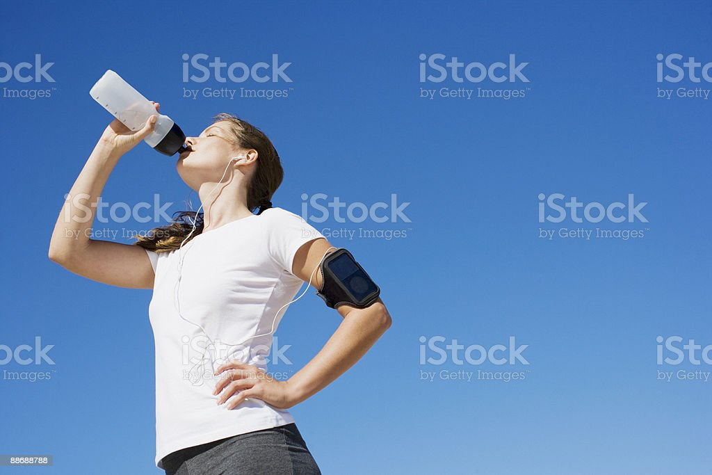 Woman runner drinking from water bottle 免版稅 stock photo