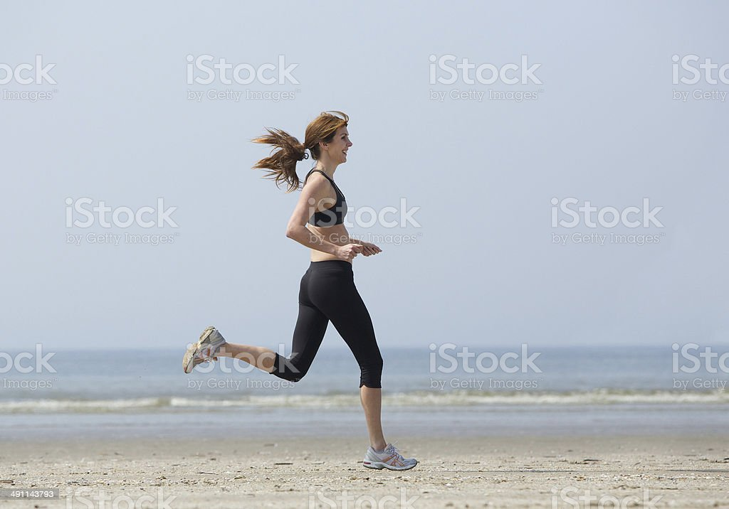 Woman runner enjoying exercise at the beach stock photo