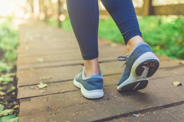 Woman runner feet walking in nature. Close up on shoes. Healthy lifestyle fitness concept. Close up of female legs with running shoes on wooden footpath in woods. Nature and sport healthy lifestyle concept. walking stock pictures, royalty-free photos & images