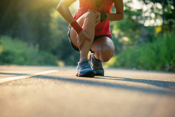 Woman runner got sports injury running on forest trail stock photo
