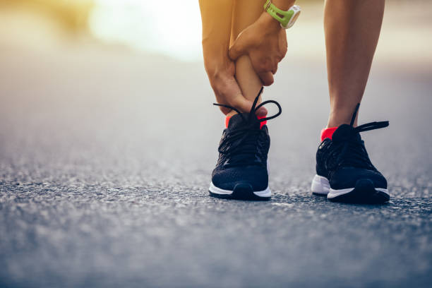 woman runner hold her injured leg on road stock photo