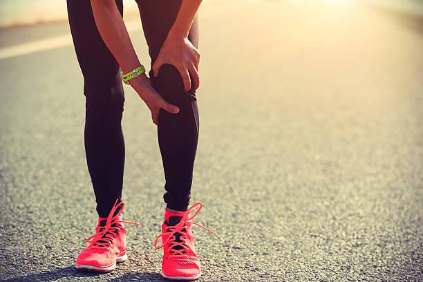 Mujer corredor Organice sus heridas pierna en la ruta - foto de stock