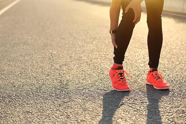 frau läufer halten ihr die verletzte bein auf road - wadenkrämpfe was tun stock-fotos und bilder