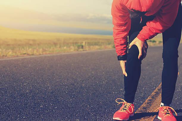Femme coureur conserver sa jambe blessée sur la route - Photo