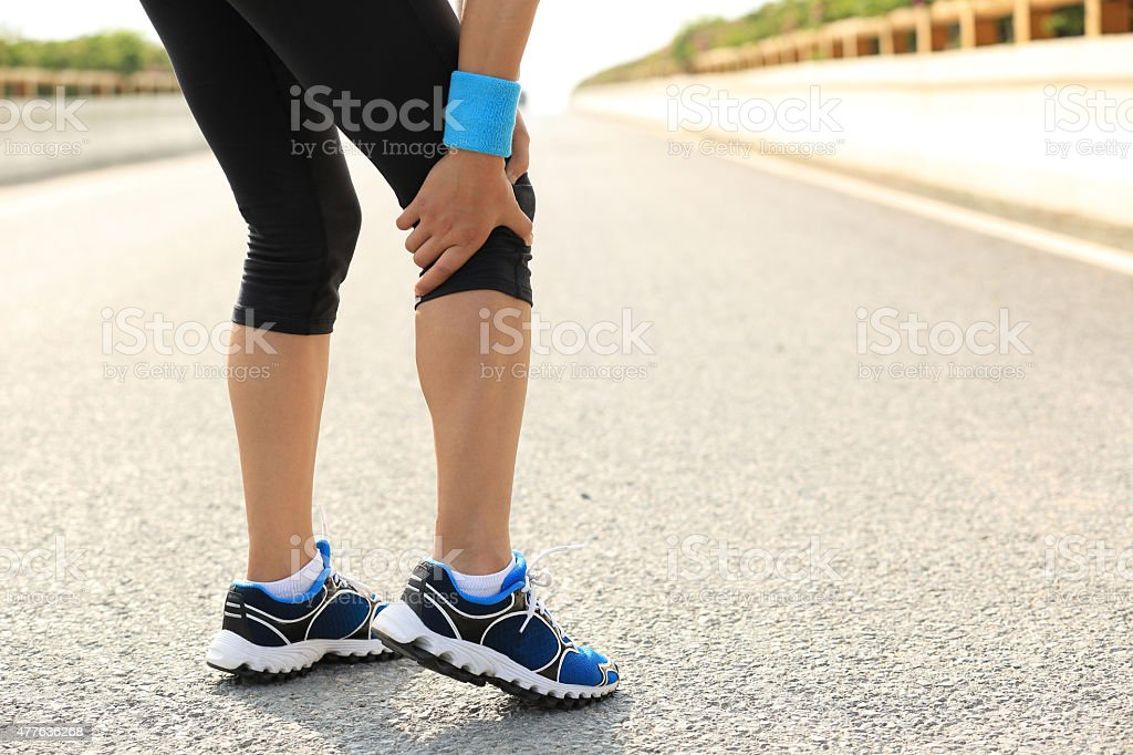 woman runner hold her injured leg stock photo