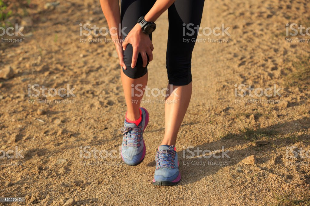 woman runner hold her sports injured knee on dirt road stock photo