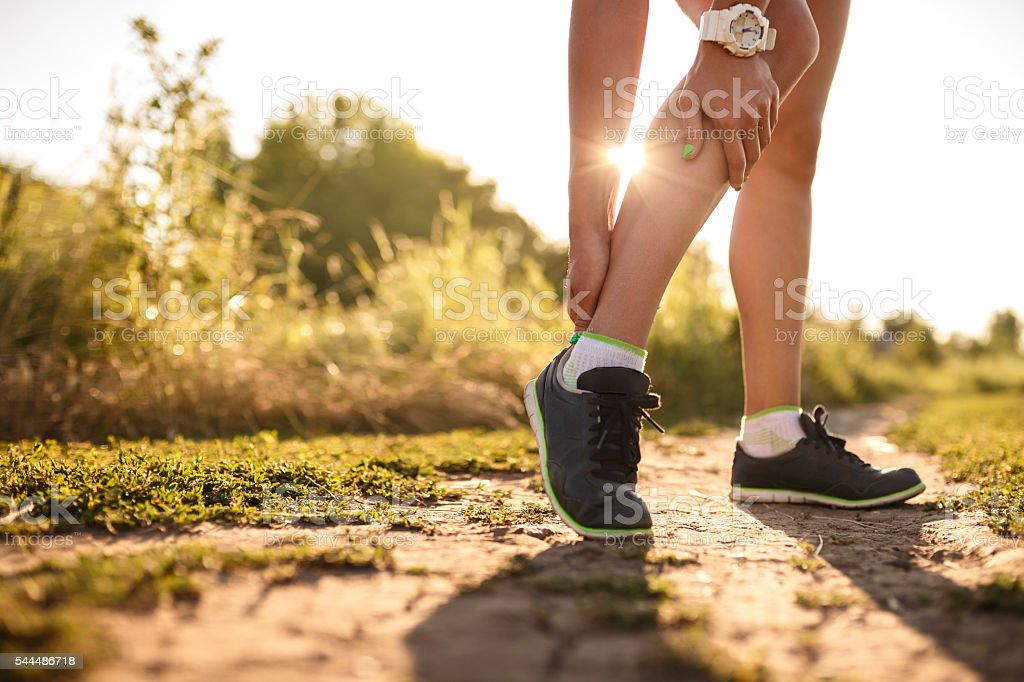 woman runner hold her sports injured leg stock photo